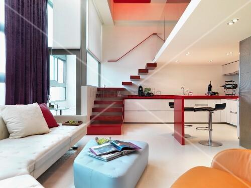 farbige polsterm bel und offene k che im modernen wohnraum mit treppenaufgang bild kaufen. Black Bedroom Furniture Sets. Home Design Ideas