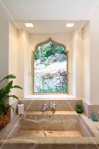 Waschbecken aus stein vor fenster mit spitzbogen im maurischen stil und gartenblick bild - Fenster zumauern welcher stein ...