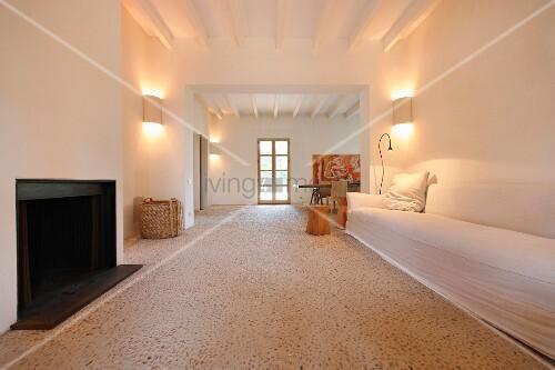 steinboden mit kleinen kieselsteinen im minimalistischen wohnraum mit schlichtem sofa vor. Black Bedroom Furniture Sets. Home Design Ideas