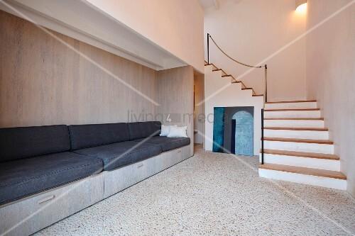 eingebaute bank mit schwarzen sitzpolstern vor holzwand und offene treppe im minimalistischen. Black Bedroom Furniture Sets. Home Design Ideas