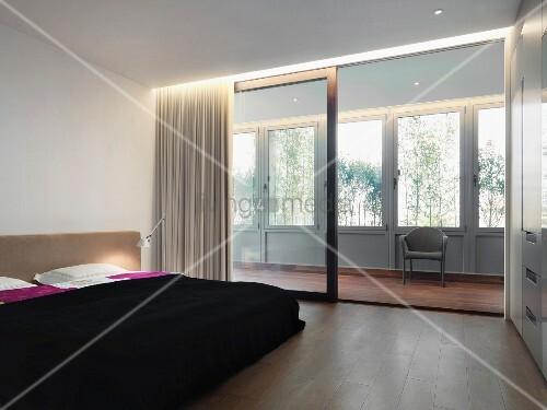 doppelbett mit schwarzer tagesdecke vor breiter schiebet rfront zu verglaster holzveranda bild. Black Bedroom Furniture Sets. Home Design Ideas