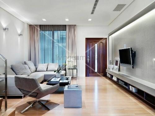 hellgraue sofagarnitur gegen ber dem fernseher an wand geh ngt und indirekter beleuchtung bild. Black Bedroom Furniture Sets. Home Design Ideas