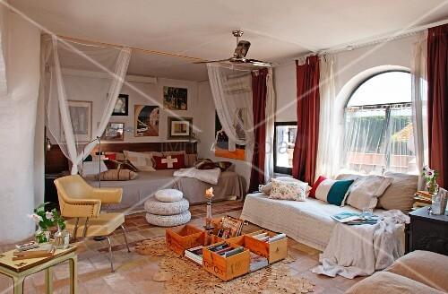 gem tliches tagesbett mit kissen am rundbogenfenster und improvisierter bodentisch vor. Black Bedroom Furniture Sets. Home Design Ideas