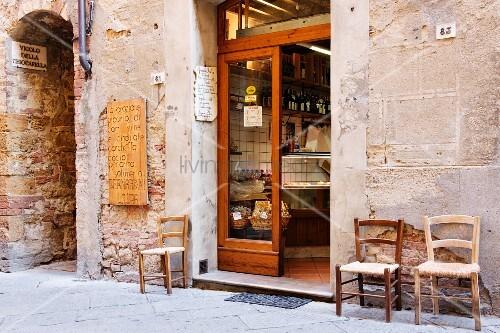 italienische metzgerei vor der t r drei alte st hle bild kaufen living4media. Black Bedroom Furniture Sets. Home Design Ideas