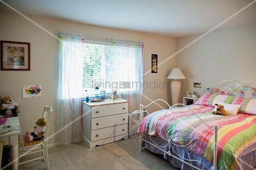 doppelbett mit bunter decke und weisse kommode unter dem fenster in einem schlafzimmer bild. Black Bedroom Furniture Sets. Home Design Ideas