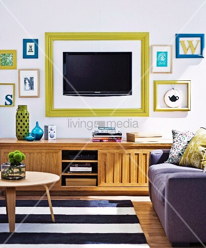 fernseher und buchstabensymbole mit bilderrahmen an der wand ber traditionellem sideboard aus. Black Bedroom Furniture Sets. Home Design Ideas