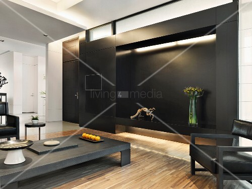 dunkler couchtisch und passender sessel vor schwarzer wand mit indirekter beleuchtung bild. Black Bedroom Furniture Sets. Home Design Ideas
