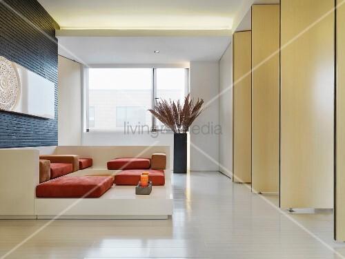 Sofa Objekt Mit Polstern Auf Podest Vor Wand Aus Drehbaren Raumteilern