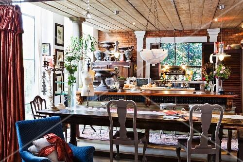 langer esstisch mit verschiedenen st hlen vor k chentheke bild kaufen living4media. Black Bedroom Furniture Sets. Home Design Ideas