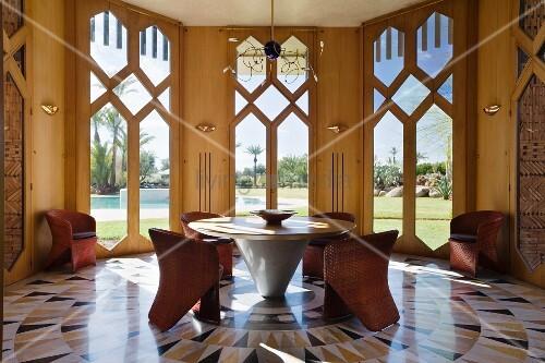 elegante sitzgruppe mit korbst hlen an rundem marmortisch auf kreisf rmigem marmorboden mit. Black Bedroom Furniture Sets. Home Design Ideas