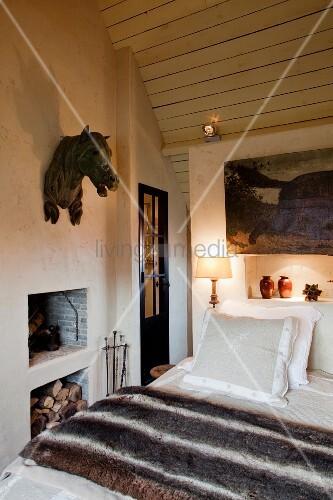 pferdekopf aus metall an der wand eines gem tlichen schlafzimmers mit kleinem kamin und. Black Bedroom Furniture Sets. Home Design Ideas