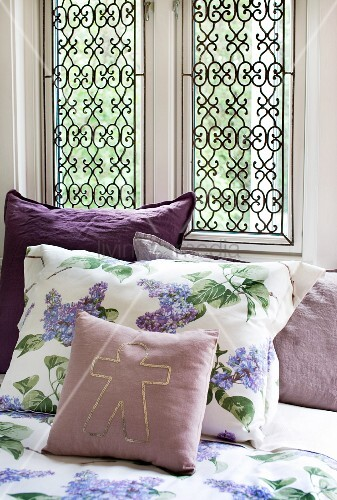 sommerliche bettw sche mit fliedermotiv dazwischen violette zierkissen bild kaufen living4media. Black Bedroom Furniture Sets. Home Design Ideas