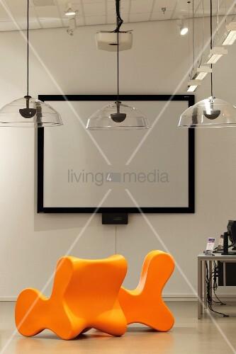 leuchtend orange st hle und transparente h ngeleuchten vor einer leinwand mit schwarzer rahmung. Black Bedroom Furniture Sets. Home Design Ideas