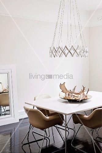 designer h ngeleuchte ber esstisch mit hirschgeweih auf schale und lederst hle im fiftiesstil. Black Bedroom Furniture Sets. Home Design Ideas