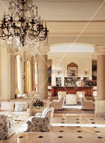 hotellobby mit klassischen polstersesseln auf gl nzendem marmorboden ionische s ulen und. Black Bedroom Furniture Sets. Home Design Ideas