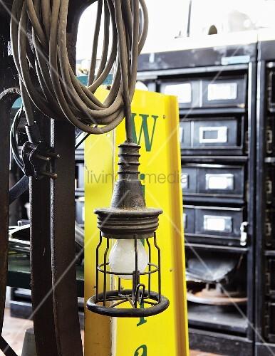 vintage lampe mit aufgerolltem kabel und werbetafel aus gelbem blech vor schubladenschrank. Black Bedroom Furniture Sets. Home Design Ideas