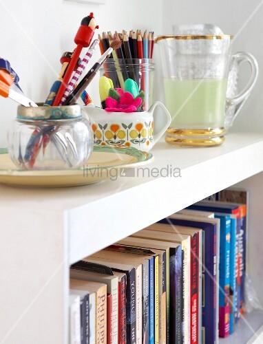 schreibutensilien in beh ltern auf weissem regal mit b chern bild kaufen living4media. Black Bedroom Furniture Sets. Home Design Ideas