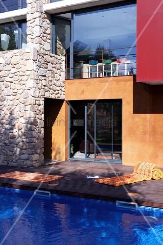 Modernes haus mit glasfronten und natursteinmauern davor for Modernes haus schweiz
