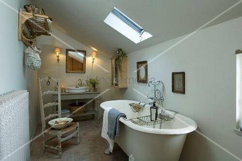 einfaches badezimmer unter dem dach mit freistehender antiker badewanne und einem binsenstuhl. Black Bedroom Furniture Sets. Home Design Ideas