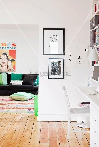 wei er arbeitsplatz vor wohnzimmer mit schwarzem sofa und naturbelassenem holzdielenboden bild. Black Bedroom Furniture Sets. Home Design Ideas