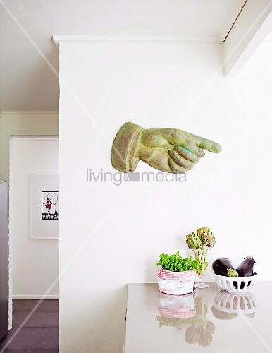 handskulptur mit ausgestrecktem zeigefinger an weisser wand ber der k chentheke bild kaufen. Black Bedroom Furniture Sets. Home Design Ideas
