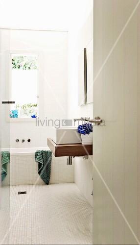 blick in ein weisses badezimmer mit waschtisch und badewanne unter dem fenster bild kaufen. Black Bedroom Furniture Sets. Home Design Ideas