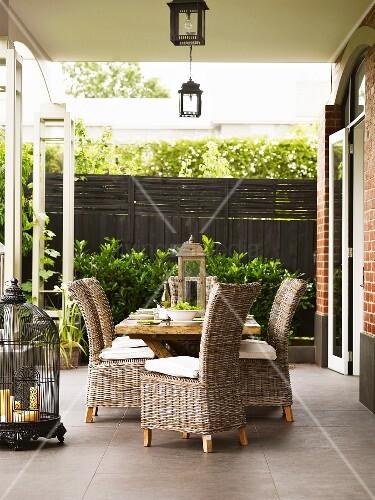 Holztisch mit korbst hlen auf terrasse mit antiquierten dekoelementen bild kaufen living4media - Holztisch terrasse ...