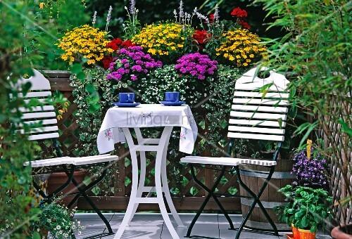 weisse st hle und tisch vor blumenkasten auf einem balkon bild kaufen living4media. Black Bedroom Furniture Sets. Home Design Ideas