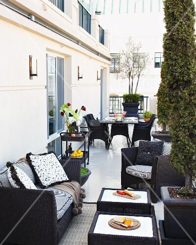 st dtische terrasse mit gem tlichen lounge m bel aus dunklem rattan und snacks auf den tischen. Black Bedroom Furniture Sets. Home Design Ideas