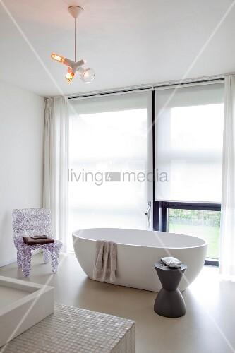 helles badezimmer mit freistehender badewanne raumhohem fenster und designerstuhl im. Black Bedroom Furniture Sets. Home Design Ideas
