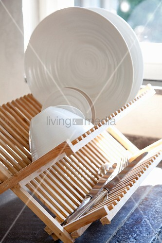 weisses geschirr und silbermesser auf abtropfgestell aus. Black Bedroom Furniture Sets. Home Design Ideas