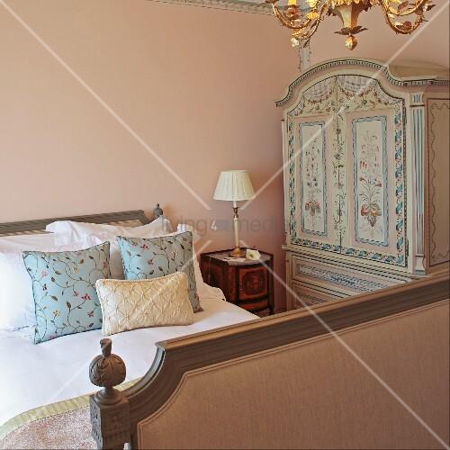 gemusterte kissen auf antikem schlittenbett und mit blumenmotiven bemalter kleiderschrank in. Black Bedroom Furniture Sets. Home Design Ideas