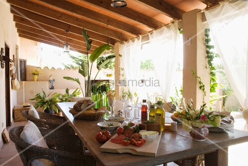 brotzeit auf der veranda gedeckter terrassentisch unter holzdach bild kaufen living4media. Black Bedroom Furniture Sets. Home Design Ideas