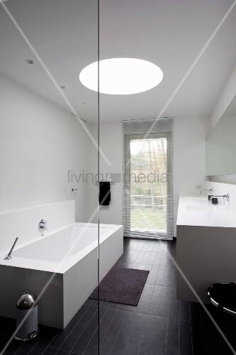 blick durch glaswand auf kubische badewanne und schwarzer fliesenboden vor terrassent r im. Black Bedroom Furniture Sets. Home Design Ideas