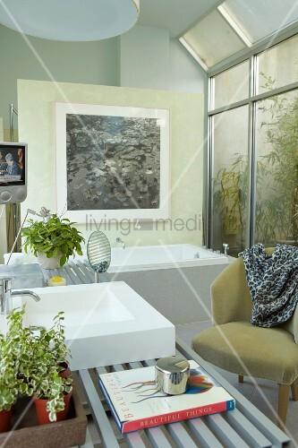 modernes bad mit sessel im retrostil vor glaswand und blick auf gartenpflanzen bild kaufen. Black Bedroom Furniture Sets. Home Design Ideas