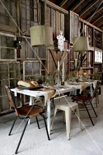 festlich gedeckter tisch unter h ngeleuchten vor improvisierter holzwand aus fensterrahmen und. Black Bedroom Furniture Sets. Home Design Ideas