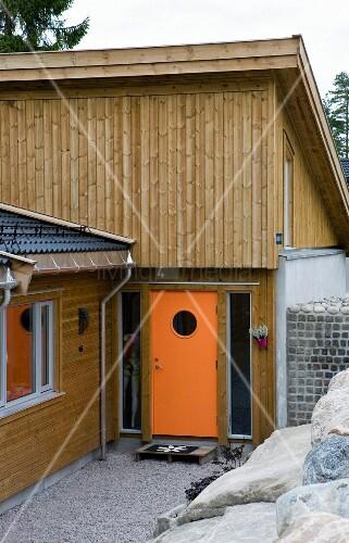 modernes holzhaus mit orangefarbener hauseingangst r bild kaufen living4media. Black Bedroom Furniture Sets. Home Design Ideas