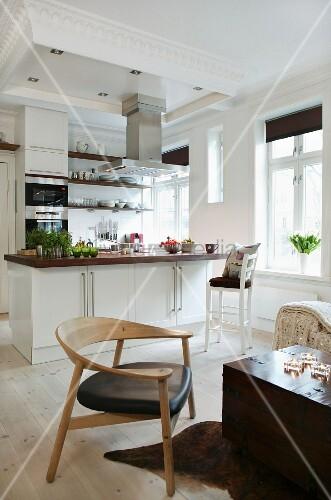 moderner holzstuhl vor kastenartigem couchtisch und offene k che mit mittelblock im wohnraum. Black Bedroom Furniture Sets. Home Design Ideas