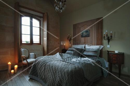 doppelbett mit moderner steingrauer tagesdecke im kontrast zur holzvert felung am kopfende. Black Bedroom Furniture Sets. Home Design Ideas