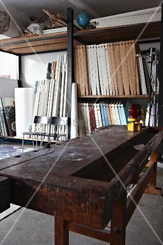 alte werkbank vor regalen mit holzelementen in loft werkstatt bild kaufen living4media. Black Bedroom Furniture Sets. Home Design Ideas