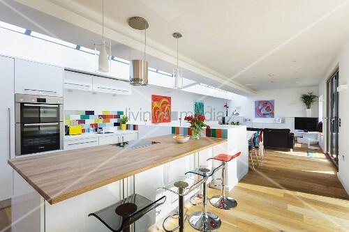 k chentheke mit hellem holz als arbeitsplatte und barhockern in offenem wohnraum bild kaufen. Black Bedroom Furniture Sets. Home Design Ideas