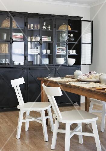 weisse k chenst hle mit retro flair an rustikalem holztisch und vitrine aus schwarzem metall. Black Bedroom Furniture Sets. Home Design Ideas