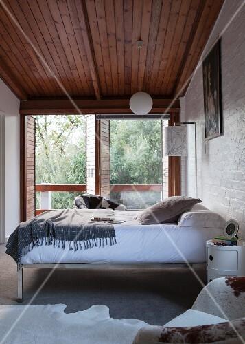 bett mit chrom metallgestell an wand neben terrassent ren in schlichtem schlafzimmer mit. Black Bedroom Furniture Sets. Home Design Ideas