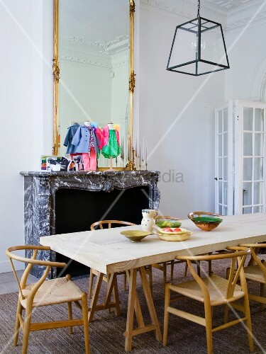 klassiker holzst hle an schlichtem esstisch aus holz vor kamin mit steinsch rze unter hohem. Black Bedroom Furniture Sets. Home Design Ideas