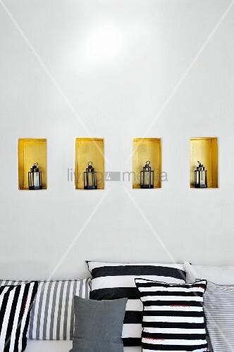 schwarz weiss gestreifte kissen auf sitzbank vor wand mit laternen in kleinen goldfarbenen. Black Bedroom Furniture Sets. Home Design Ideas