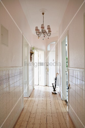 elegant narrow hallway with chandelier half height tiled