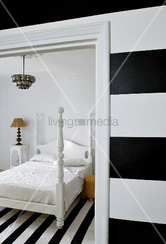 schwarz weiss gestreifte wand blick durch offene t r auf bett mit weiss lackierten holzgestell. Black Bedroom Furniture Sets. Home Design Ideas