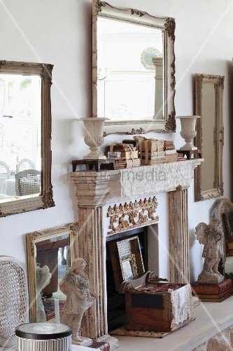 kamin mit profiliertem sims unter gerahmtem wandspiegel an wand zwischen antiken skulpturen auf. Black Bedroom Furniture Sets. Home Design Ideas