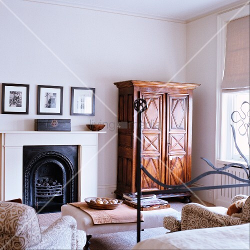 teilweise sichtbares bett mit metallgestell gegen ber offenem kamin und biedermeier schrank in. Black Bedroom Furniture Sets. Home Design Ideas