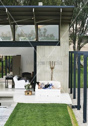 terrasse mit lesender frau auf sofa vor architektenhaus mit sichtbetonfassade und leichtem. Black Bedroom Furniture Sets. Home Design Ideas